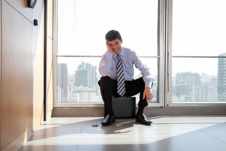 relieved: Portrait of happy young male entrepreneur sitting on briefcase