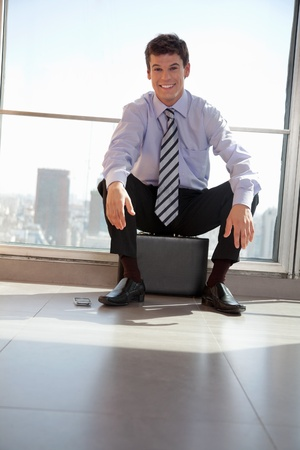relieved: Portrait of handsome young male executive sitting on briefcase