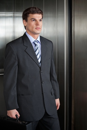people in elevator: Confident businessman walking out from elevator holding briefcase