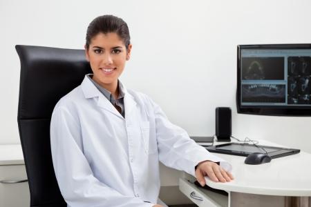 especialistas: Retrato de Mujer dentista muy sentada en su escritorio con los dientes de rayos X en la pantalla Foto de archivo