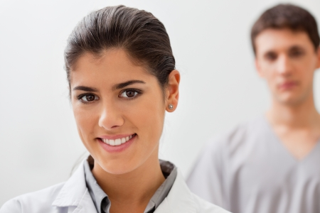 dental hygienist: Portrait of smiling female doctor with practitioner standing in background