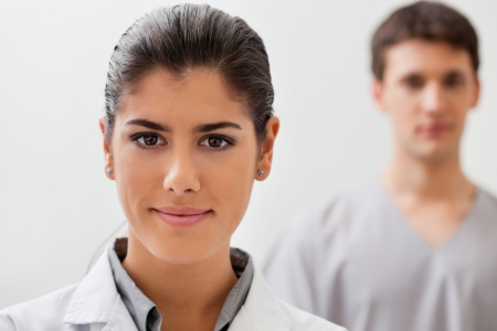 Portrait of pretty female doctor with practitioner standing in background photo