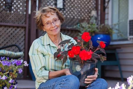 Portrait of beautiful senior woman holding potted plant photo