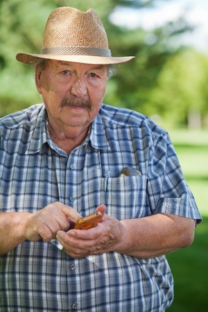 Portrait of senior man text messaging in park Stock Photo - 11538768
