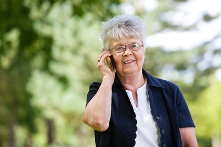 Portrait of smiling senior woman having conversation on mobile phone photo