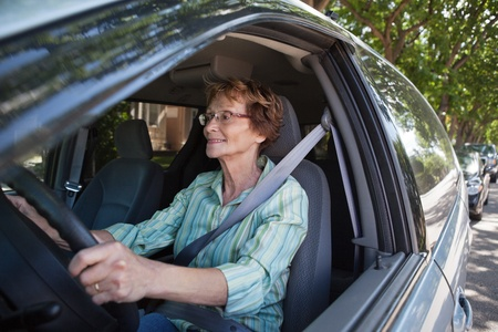 Active senior woman smiling while driving car photo