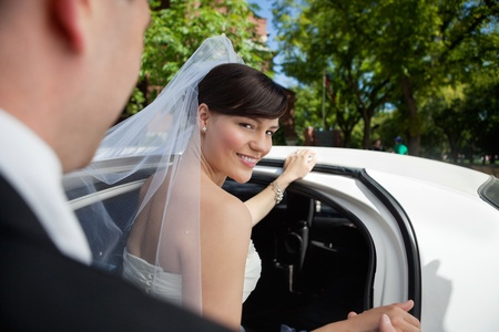 Portrait of beautiful bride getting in limousine photo