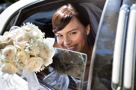 Happy bride sitting in limousine holding out flower bouquet