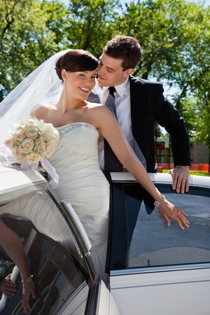Wedding couple in Limo, groom about to kiss bride photo