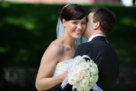 sneaks: Groom sneaks a kiss on brides cheek Stock Photo