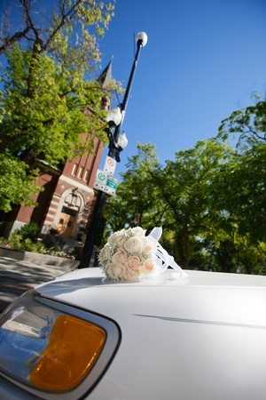 Wedding flowers on car parked in front of church photo