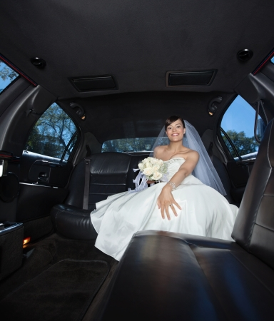 Attractive bride sitting in limousine holding flower bouquet photo