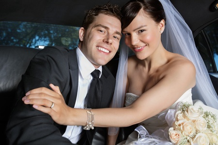 newlywed: Portrait of newlywed couple smiling sitting in limousine Stock Photo