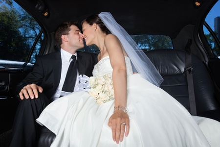 Loving newlywed bride and groom in limousine photo