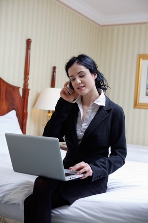 Business woman talking on cell phone while working on laptop photo