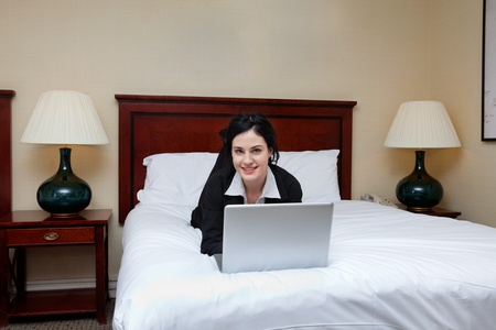 Portrait of young beautiful businesswoman lying on bed with laptop in a hotel room photo
