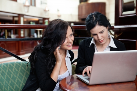 Female executive working on laptop while her colleague talking on cell phone photo
