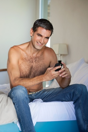 male age 40's: Portrait of shirtless man using cell phone