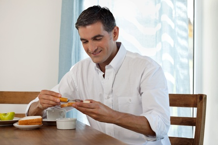 male age 40's: Middle aged man having breakfast at home