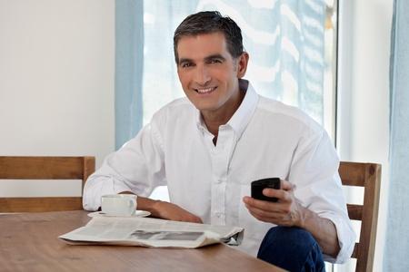 vecchiaia: Man lettura giornale del mattino e Controllo Phone