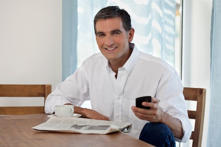 mid adult man: Man Reading Morning Newspaper and Checking Phone Stock Photo