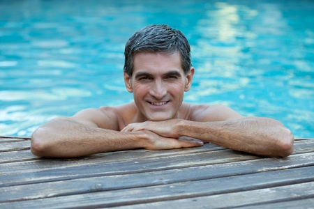 male age 40's: Portrait of smiling man relaxing by the swimming pools edge Stock Photo