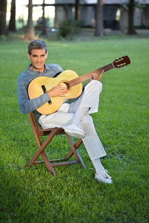 Portrait of casual middle aged man playing guitar sitting in lawn photo