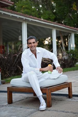 wealthy lifestyle: Relaxed mezza et� l'uomo sorridente con succo fresco