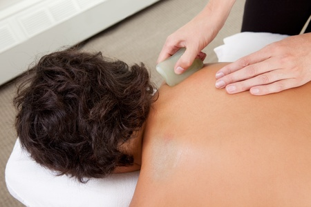 sha: Young male receiving Gua Sha treatment on back and shoulders