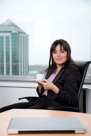 Portrait of smart business woman having cup of coffee at office photo