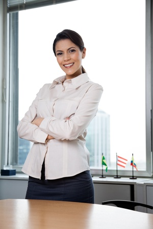 Portrait of smiling businesswoman with arms crossed standing in office photo