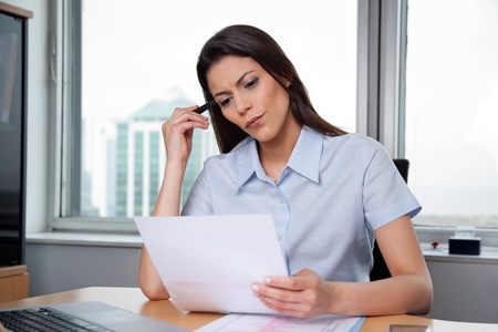Thoughtful businesswoman reading important business papers photo