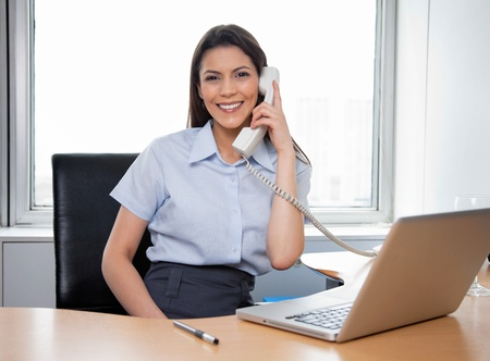 Portrait of smiling businesswoman talking on phone with laptop on her desk photo