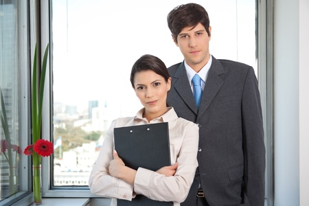 Portrait of female executive standing with male executive photo