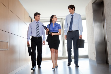 Professional businesspeople walking in office corridor photo
