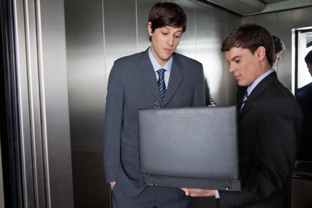 Male in suit showing something in the briefcase to his colleague photo