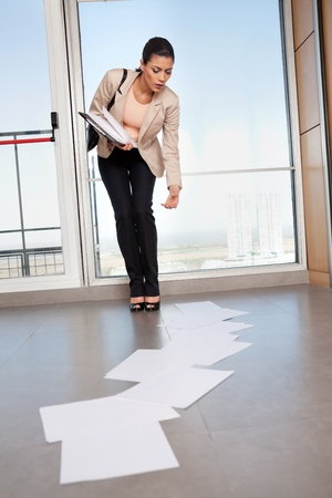 pick: Beautiful business woman bending down to collect scattered papers on floor Stock Photo