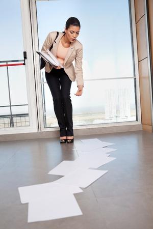 bending down: Hermosa mujer de negocios agach�ndose para recoger papeles esparcidos en el suelo Foto de archivo