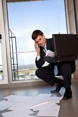 bending down: Hombre empresario agacharse para recoger papeles dispersos mientras habla por tel�fono celular