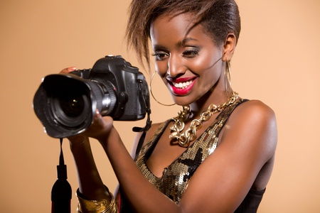 Attractive model in studio holding DSLR camera photo