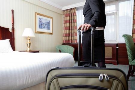 femme avec valise: Femme debout avec des bagages en chambre d'h�tel