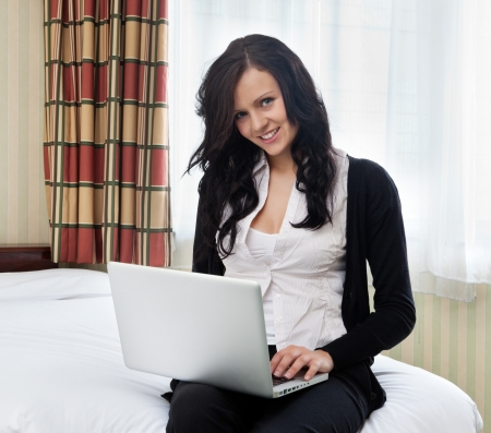 Portrait of beautiful businesswoman using laptop sitting in hotel room photo