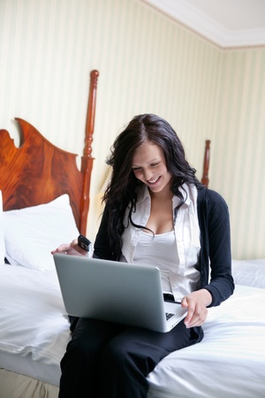 Young smiling businesswoman using laptop while sitting on bed photo