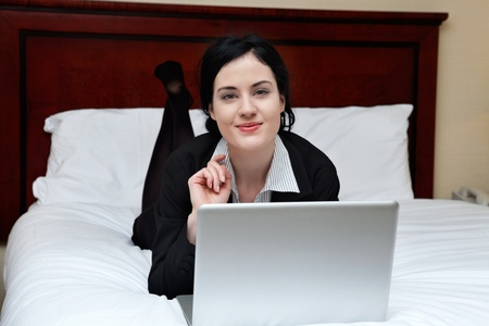hotel suite: Portrait of young smiling business woman lying on bed with laptop in a hotel room Stock Photo