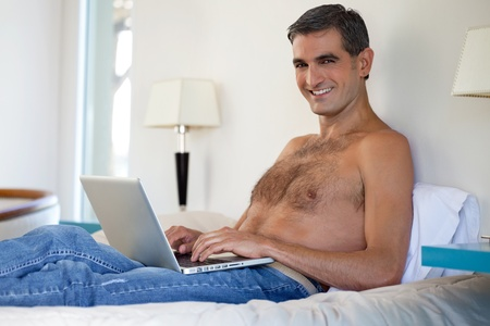 male age 40's: Portrait of smiling shirtless middle aged man working on laptop