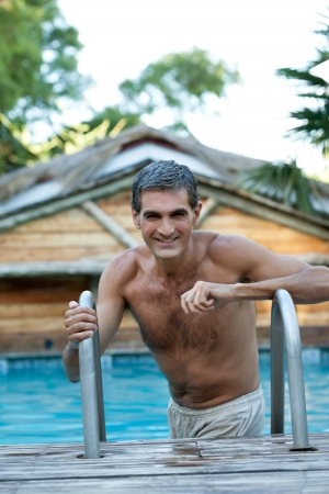male age 40's: Portrait of smiling middle aged man standing in the pool
