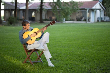 Full length of casual relaxed middle aged man playing guitar in the lawn photo