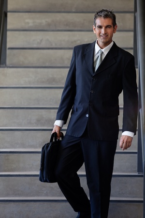 Portrait of smart male entrepreneur walking down the stairs photo