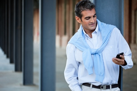 Smart casual man using cell phone with hand in pocket photo