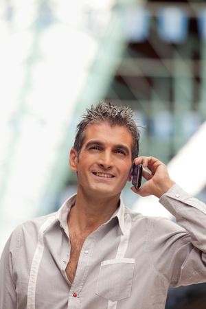 mid adult men: Smart middle aged man talking on mobile phone